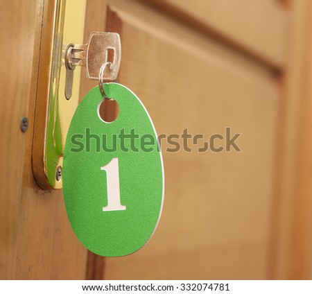 Door handles on wood wing of door and key in keyhole with numbered label - stock photo