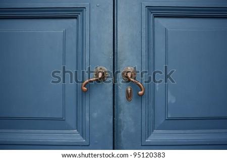 Door handles with an old double wood door blue color - stock photo