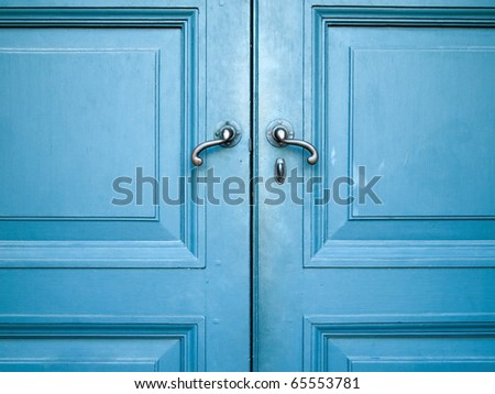 Door handles with an old double wood door painted with blue - stock photo