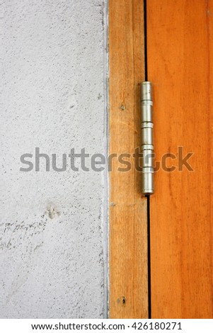 Door hinges with wooden door and concrete wall. - stock photo