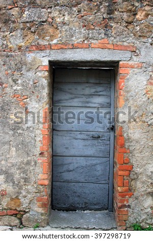 Door in a stone wall in Tuscany - stock photo