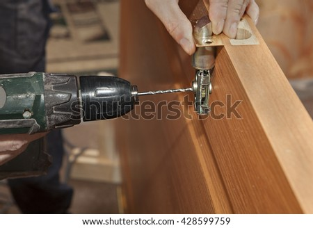 Door installation, installing deadbolt lock using power drill, close-up. - stock photo