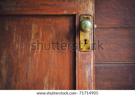Door knob and keyhole made of brass On the old wooden door - stock photo