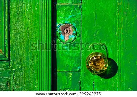 Door knob made of glass, retro doorway painted in green closeup - stock photo
