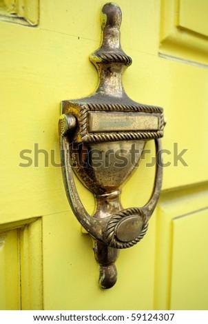 Door knock on a yellow wooden door - stock photo