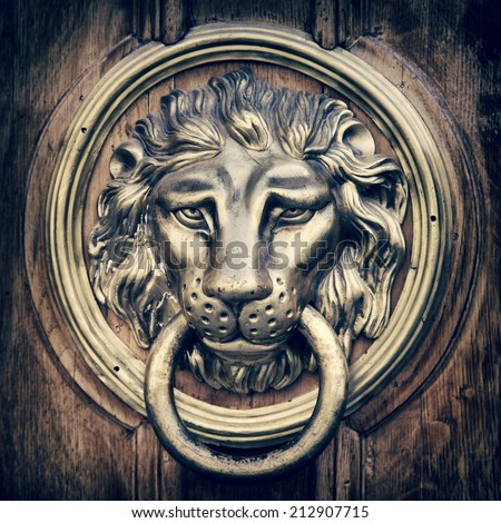 Door knocker, handle - lion head. Vintage stylized photo. - stock photo