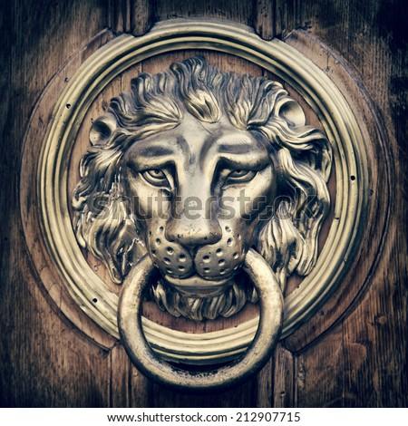 Door knocker, handle - lion head. Vintage stylized photo. - stock photo
