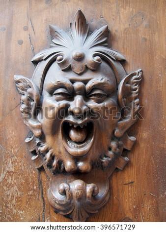 Door knocker on an old wooden door in Siena, Italy. - stock photo