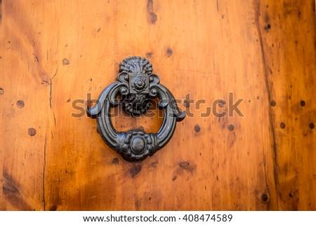 Door knocker on an old wooden door in Tuscany - Italy - stock photo