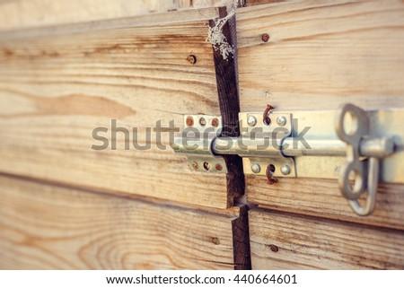 Door latch on a wooden door. Wooden planks nailed - stock photo