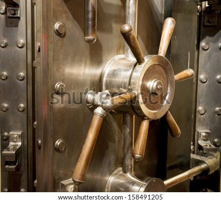 Door of big vintage safe in retail store bank vault security valuable storage - stock photo