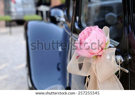 Door of black wedding car with flower and white bow rear view - stock photo