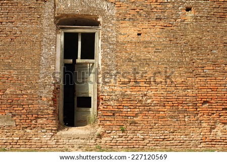 door on abandoned castle, detail on ancient facade - stock photo
