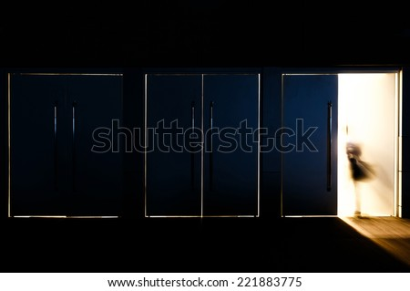 Door opened with motion blur of a man and light coming through the space - stock photo