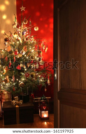 Door opening into a room decorated for Christmas  - stock photo