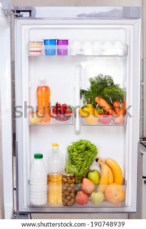 Door refrigerator with fresh fruits and vegetables - stock photo