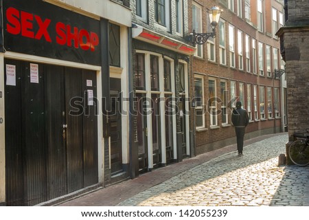 Door to sex shop and man in narrow pathway  in Amsterdam. Old town of Netherlands Capital. - stock photo