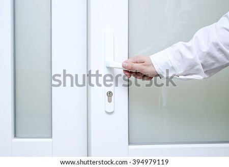 door to the room, medical examination, doctor or nurse opens the door to the Chamber, Hand in a white coat, door handle - stock photo