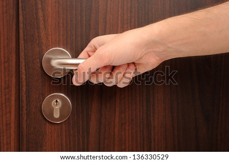door with a hand on handle - stock photo