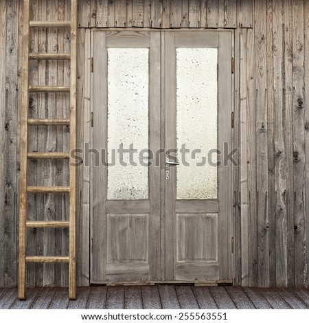 door with frosty window and ladder near the plank house wall background - stock photo