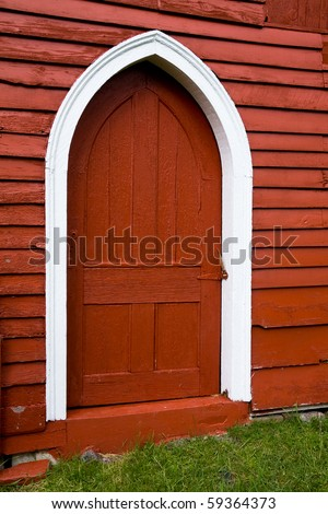 Door with Gothic arch in old red wooden barn. - stock photo