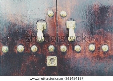 door with hand-shaped knobs