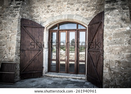 Door with shuttered in an old stone building. - stock photo