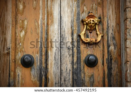 Doorknob on an old wooden door. Tuscany, Italy