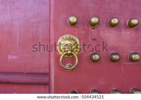 Doorknob with brass lion head of ancient Chinese red door of palace