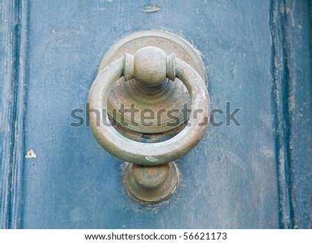 Doorknocker on blue wooden frontdoor.
