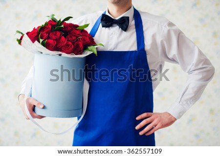 Doorman with bouquet of red roses in box. Delivery of flowers. - stock photo