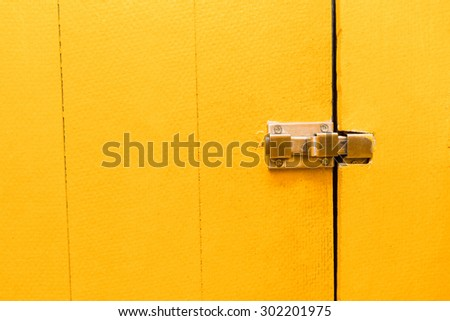 Doors, bright yellow, and a lock. - stock photo