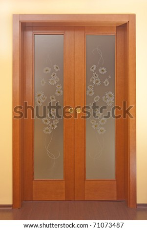 Doors with painted glass on yellow wall - stock photo