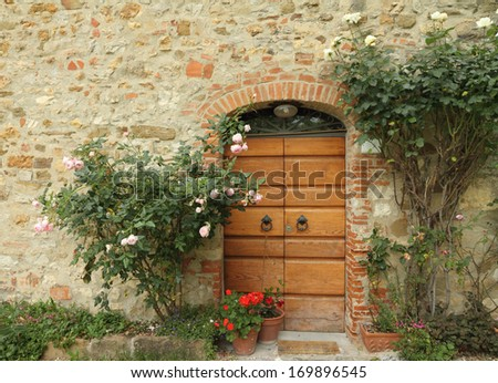 doorway decorated with climbing roses to the tuscan house - stock photo
