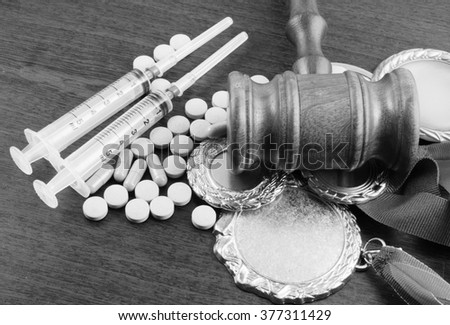 Doping in sport. Gavel, medals and tablets with syringes on table
