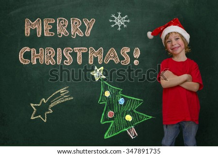 dorable little boy with Santa hat standing in front of a scratched green blackboard, smiling, head sideways. Marry Christmas banner, Christmas tree, star and snowflakes chalk drawing - stock photo
