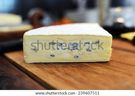 Dorblu cheeses on old wooden kitchen board.