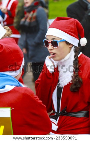 DORDRECHT, NETHERLANDS - DECEMBER 21, 2013: Young Santa wearing stars and stripes sunglasses waiting for the run to begin. Santa run is organized every year to raise money for Dordrecht Rotary Club