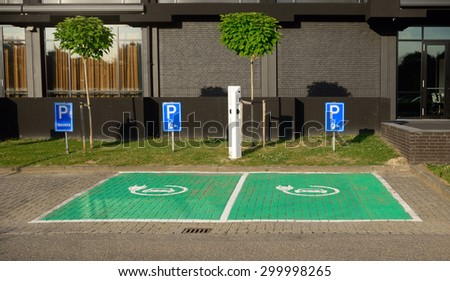 DORDRECHT, NETHERLANDS - JULY 13, 2015: Plug-in hybrid and electric vehicle designated, green-painted parking spaces with charging station for guests at a modern Postillion hotel.   - stock photo