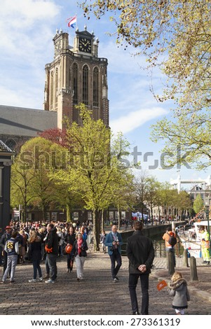 DORDRECHT, THE NETHERLANDS - APRIL 27, 2015: Crowds gather by Dordrecht cathedral awaiting the visit of the Dutch royal family during the traditional Kings Day celebrations. - stock photo
