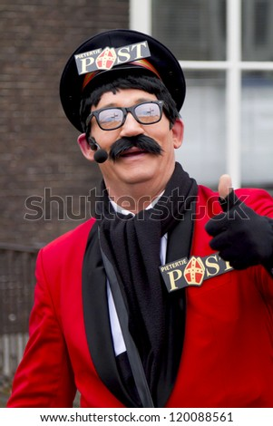 DORDRECHT, THE NETHERLANDS - NOVEMBER 18: Man dressed as the postman of Santa Claus giving a thumbs up to the public on November 18, 2012 in Dordrecht, Netherlands. - stock photo