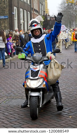 DORDRECHT, THE NETHERLANDS - NOVEMBER 18: Motorcycle policeman dressed in costume waving to the children on November 18, 2012 in Dordrecht, Netherlands. He is escort to Santa Claus in a parade. - stock photo