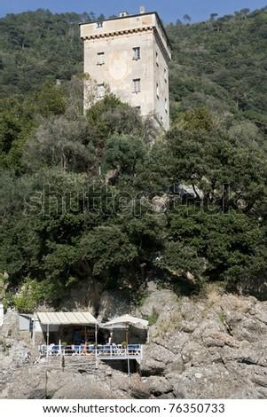 Doria Tower over beach restaurant,  Camogli, San Fruttuoso abbey bay - Portofino Natural Park - stock photo