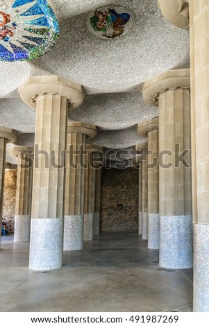 Doric columns hold the central terrace with serpentine seating in Parc Guell designed by Antoni Gaudi. Carmel Hill, Barcelona, Spain.