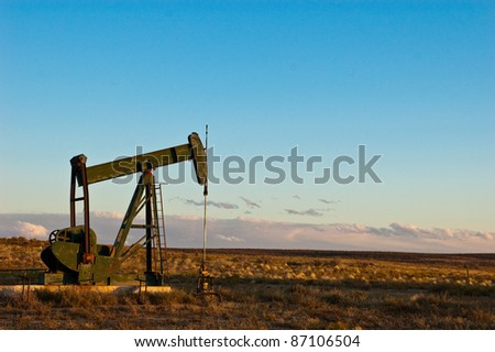 Dormant oil or natural gas pump alone on vast prairie with storm clouds in the distance - stock photo