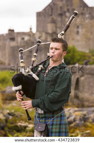 DORNIE, SCOTLAND - AUGUST 24, 2004: Bagpiper performs in front of Eilean Donan Castle at Loch Duich in Glen Shiel.