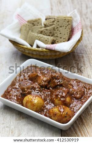 doro wat (spicy ethiopian chicken stew) and injera - stock photo