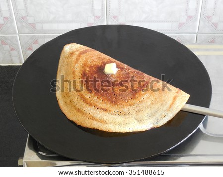 Dosa, Indian vegetarian food, with a butter topping, being prepared on a skillet. - stock photo