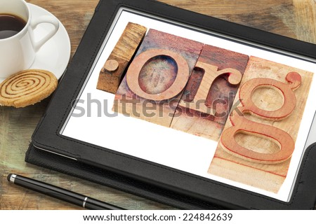dot org internet domain for non-profit organization in letterpress wood type printing blocks on a digital tablet screen with a cup of coffee - stock photo