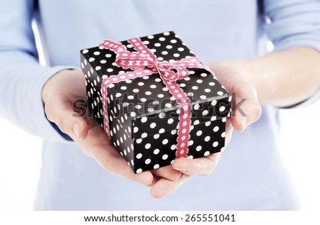 dotted present box with ribbon in a woman hand - stock photo